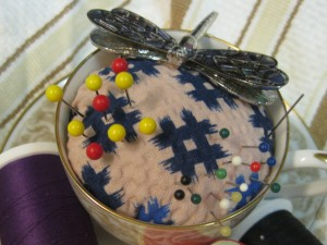 """My teacup & saucer are 3"""" high. The pattern on the fabric remnds me of tic-tact-toe. The dragon fly is a lapel pin I bought in New Zealand. I put it here because the latch never worked and it kept falling off."""