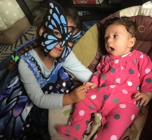 Big sister dressed up as a butterfly for Halloween. In this photo it looks like Sissy is surprised at her older sister's costume.