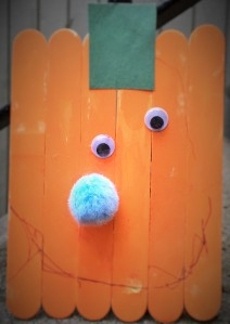 This pumpkin was made with supplies from the Dollar Store: jumbo popsicle sticks, pom poms and googly eyes. I had the orange paint, magnet, and green cpaper.